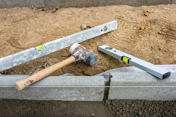 Randsteine setzten Randstein einklopfen und Betonstützen anbringen